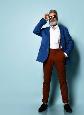 Gray-haired, bearded man in white shirt, jacket, brown pants and suspenders, black loafers. He straightening his sunglasses, put his hand in pocket, posing on blue background. Full length, copy space