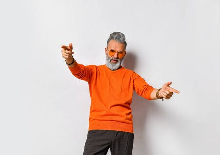 Gray-haired, bearded, aged male in orange sweater and sunglasses, black pants, bracelets. Pointing at you by his forefingers, posing isolated on white. Fashion and style. Close up, copy space 版權商用圖片