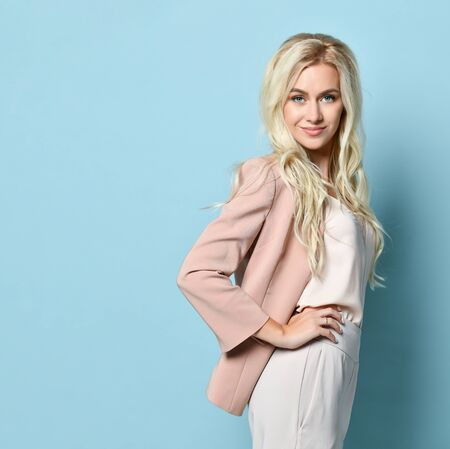 Blonde woman in beige jacket and white overall. There is watch on her hand. Smiling, touching her hair, posing standing sideways against blue studio background. Beauty, fashion. Copy space. Close-up Stock Photo - 142763248