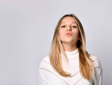 First kiss, unwanted kiss concept. Closeup portrait of young woman face rying to kiss you camera, isolated light white background Foto de archivo