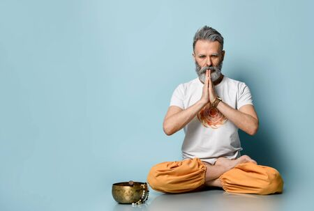 Gray-haired male, Hare Krishna follower, in traditional orange and white dhoti clothes. Praying, sitting on floor in lotus pose on blue background. Singing bowl, rosary nearby. Close up, copy space