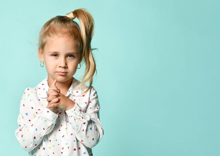 Blonde schoolgirl with ponytail, dressed in shirt with hearts print. She looking thoughtful, showing her forefinger, posing on blue background. Childhood, fashion, advertising. Close up, copy space