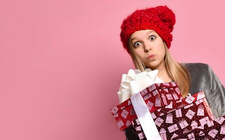 Blonde teenager in gray plush pajamas and red hat with pompom. She holding colorful gift boxes tied with white ribbon, kissing you, posing on pink background. Christmas holidays. Copy space. Close up