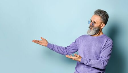 Gray-haired, bearded, elderly man in sunglasses and purple sweater. Showing something by his hands and looking at it while posing against blue background. Fashion and style. Close up, copy space