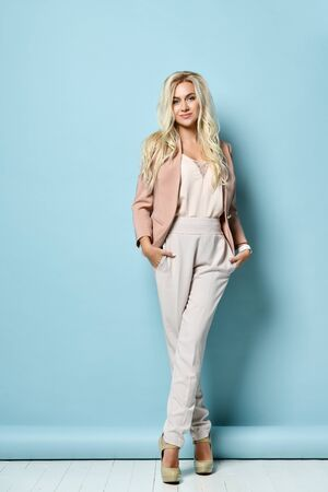 Blonde model with long hair, in beige jacket, white overall, high heels. There is watch on her hand. Smiling, posing standing against blue studio background. Beauty, fashion. Copy space. Full length Stock Photo