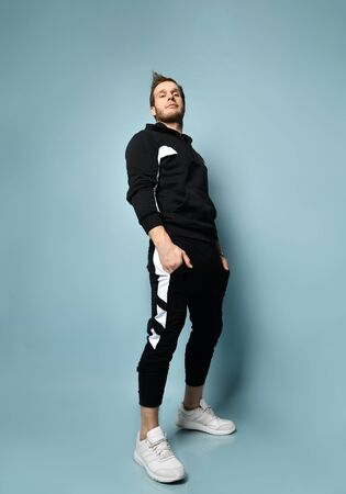 Handsome hipster male with cool hairstyle, in black tracksuit, bracelet and white sneakers. He is rolling up his sleeve, posing against blue studio background. Trendy outfit. Full length, copy space Foto de archivo