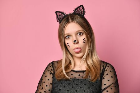 Blonde teenager in black dress, headband in form of cat ears, face painting. She is showing her tongue, posing on pink background. Beauty, fashion, advertising. Copy space. Close up Stok Fotoğraf