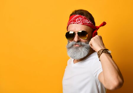 Gray-bearded, brunet grandpa in sunglasses, red bandana, white t-shirt and bracelet. He straightens his mustache, posing standing against orange background. Fashion and style. Close up, copy space Stock Photo