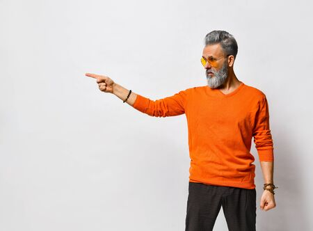 Gray-haired, bearded, elderly male in orange sweater and sunglasses, black pants, bracelets. Pointing at something by his forefinger while posing isolated on white. Close up, copy space 版權商用圖片