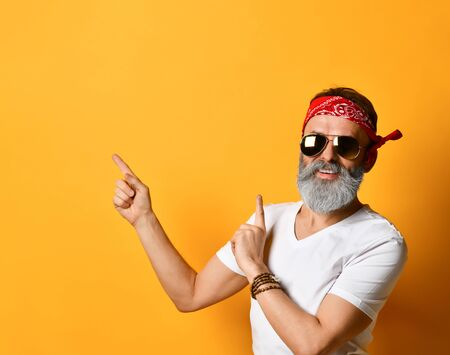 Gray-bearded, mature man in sunglasses, red bandana, white t-shirt and bracelet. He smiling, pointing at something by forefingers, posing on orange background. Fashion and style. Close up, copy space