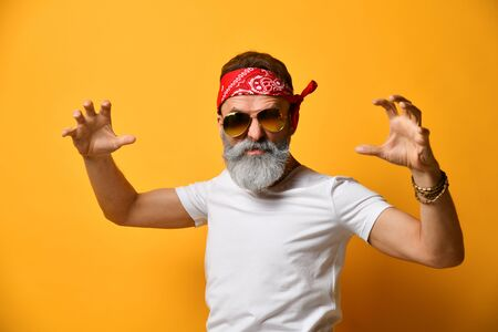 Gray-bearded, middle-aged male in sunglasses, red bandana, white t-shirt and bracelet. He scaring you with his own hands, posing on orange background. Fashion and style. Close up, copy space Stock Photo
