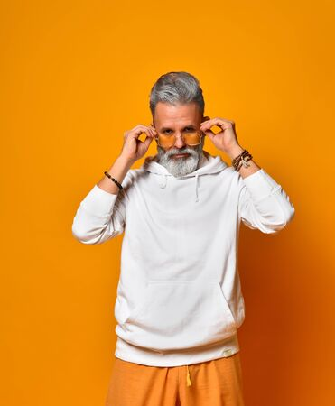 Gray-haired, bearded granddad in white hoodie, bracelets. He is fixing his orange sunglasses and looking through it while posing against orange background. Fashion and style. Close up, copy space