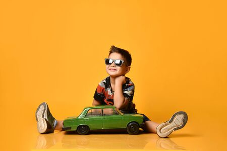 Kid in gray sunglasses, camouflage t-shirt, blue shorts, khaki sneakers. Smiling sitting on floor, legs wide apart, holding green model of retro car, posing on orange background. Close up, copy space