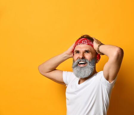 Gray-bearded, brunet, aged male in red bandana, white t-shirt and bracelet. He put his hands on head and laughing, posing standing against orange background. Fashion and style. Close up, copy space Stock Photo