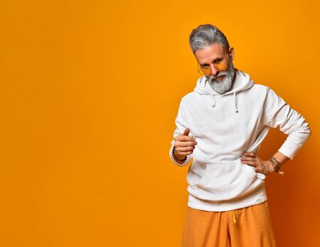 Gray-haired, bearded, aging man in white hoodie, pants and sunglasses, bracelets. Put his hand on hip and looking at you on orange background. Fashion and style. Close up, copy space