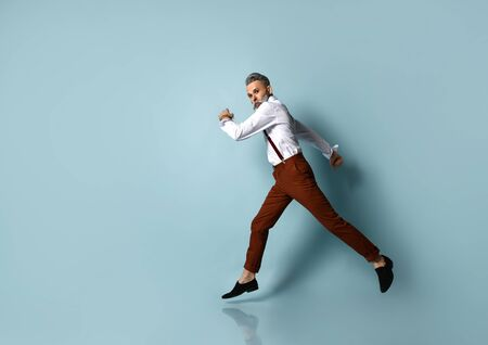 Gray-haired, bearded male in white shirt, brown pants and suspenders, black loafers. He is running, posing sideways against blue studio background. Fashion and style. Full length, copy space