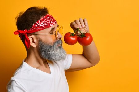 mature man in red bandana, white t-shirt, sunglasses and bracelet. He holding red tomatoes on twigs, sniffing it, posing sideways against orange background. Close up, copy space Imagens