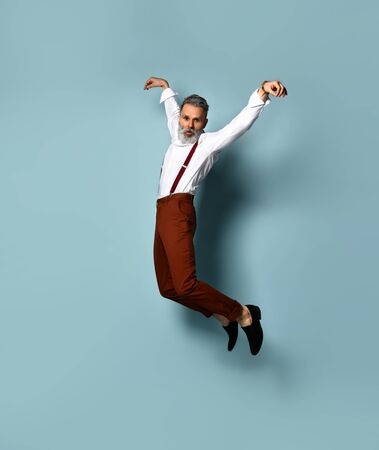 Gray-haired, bearded male in white shirt, brown pants and suspenders, black loafers. He is jumping up while posing against blue studio background. Fashion and style. Full length, copy space