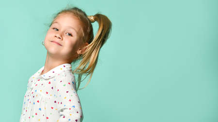 Portrait of a little blond child in a heart-shaped print shirt. She smiles, fools around, has fun against the backdrop of a mint studio. Sincere emotions, fashion, advertising.