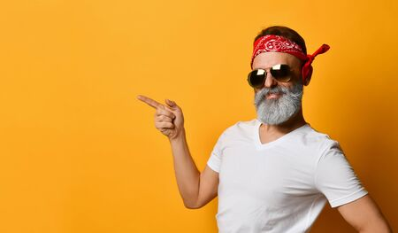Gray-bearded, brunet grandpa in sunglasses, red bandana, white t-shirt and bracelet. He is pointing at something by his forefinger, posing on orange background. Fashion and style. Close up, copy space Stock Photo