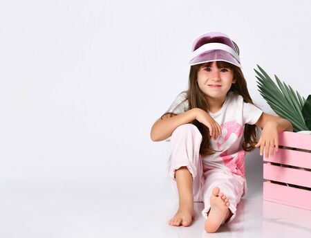 A pretty girl sits on the floor, one leg bent at the knee, in a cap and summer clothes, in the Studio, looking straight, next to a pink wooden box inside which are the leaves from the flower and a hat