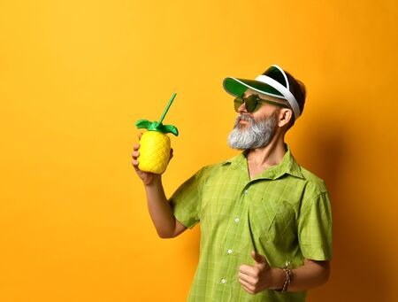 Gray-bearded grandpa in green sun visor, shirt, sunglasses. He smiling, holding cocktail bottle in form of pineapple with tube, clenched fist, posing on orange background. Close up, copy space Stok Fotoğraf