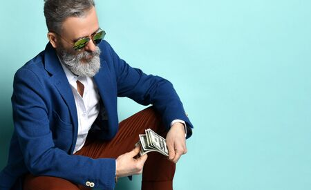 bearded elderly man in white shirt, jacket, brown pants, black loafers and sunglasses. He squatting, showing some hundred dollar bills, posing on blue background. Close up, copy space