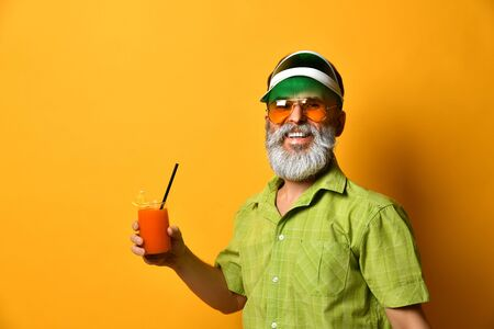 Gray-bearded man in green sun visor, shirt, sunglasses. He smiling, holding glass of fresh squeezed juice with slice of lemon and tube, clenched fist, posing on orange background. Close up, copy space