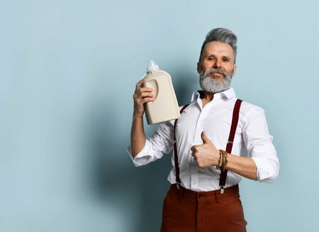 Gray-haired bearded man in white shirt, brown pants and suspenders, bracelet. Showing thumb up and plastic bottle, blank mock up of effective detergent, posing on blue background. Close up, copy space