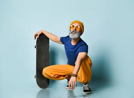 Bearded elderly man in purple t-shirt, sunglasses, orange pants and hat, gumshoes, bracelets. Looking at you, holding black skateboard, squatting on blue background. Style, sport. Close up, copy space