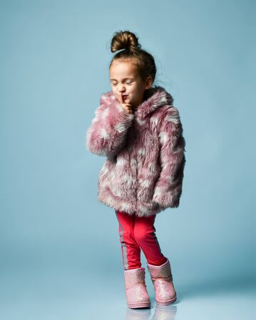 Little lady with bun hairstyle, dressed in pink faux fur coat, pants and boots. She smiling, gesticulating, posing on blue studio background. Childhood, fashion, advertising. Full length, copy space