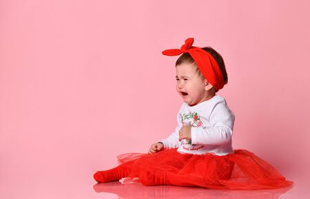 Toddler in white bodysuit, red headband, poofy skirt, tights. She crying, sitting on floor against pink studio background. Christmas, New Year, holidays. Advertising for babies. Close up, copy space