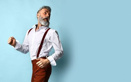 Gray-haired, bearded male in white shirt, brown pants and suspenders, black loafers. He runs looking back, posing sideways against blue studio background. Fashion and style. Full length, copy space 版權商用圖片