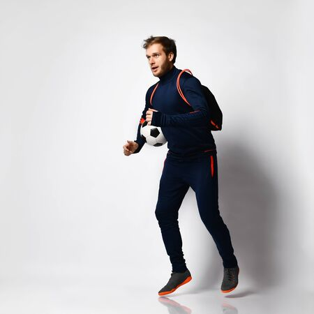 Skilled guy soccer player in blue tracksuit, colored sneakers and backpack. He is running, holding a ball, posing isolated on white. Concept of sport, balance and agility. Full-length, copy space Foto de archivo
