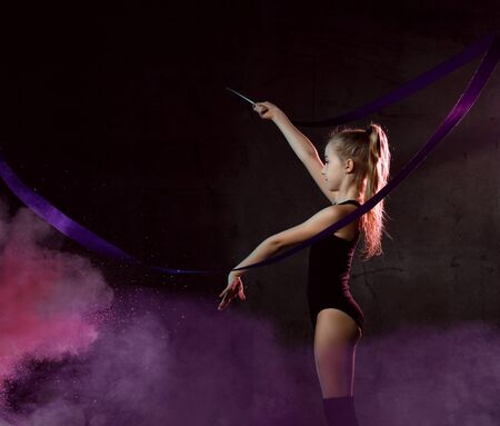 Young girl gymnast in black sport body and uppers standing sideways and making exercise with blue gymnastic tape over dark smoke background. Rhythmic gymnastics beauty concept