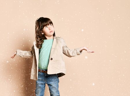 a little brunette with curls stands under snowflakes, in a beige coat. catches snowflakes with her hands. On a beige background, in the Studio.
