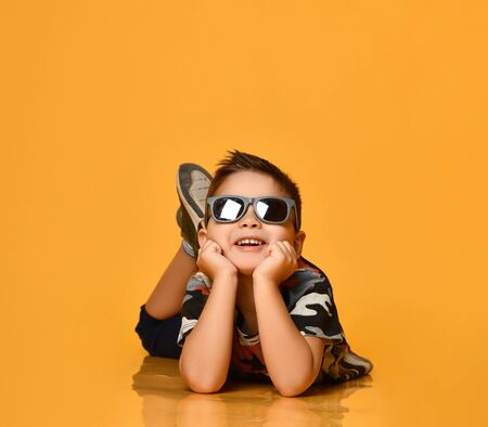 Little brunet kid in gray sunglasses, camouflage t-shirt, blue shorts and khaki sneakers. Smiling, lying on floor, propping his head with hands, posing on orange background. Close up, copy space