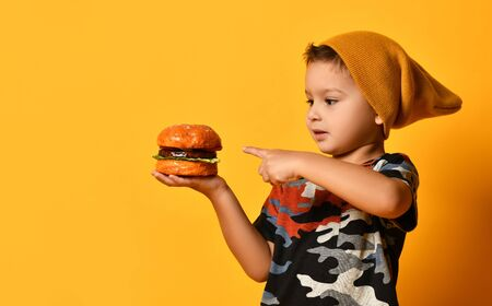 Little boy in camouflage t-shirt and terracotta hat is pointing by forefinger at hamburger on his palm, posing on orange background. Happy childhood, fast food, advertising. Close up, copy space