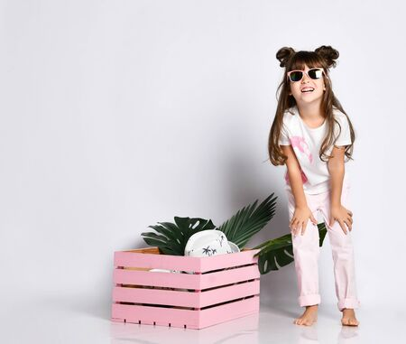 cute little girl poses next to a pink wooden box, inside of which lie the leaves of a flower and a hat. She is wearing sunglasses, summer clothes and a fashionable hairstyle, leaning forward, putting her hands on her knees and smiling sweetly