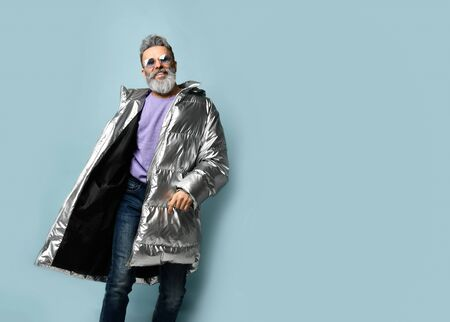 Gray-haired, bearded, mature male in purple pullover and sunglasses, silver colored down jacket, jeans. He is smiling while posing on blue studio background. Fashion, style. Close up, copy space