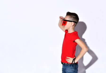 Teenage child in oversized sunglasses with protective visor, red t-shirt and black bracelets. He is looking wondered, pointing at something, posing sideways isolated on white. Close up, copy space Reklamní fotografie