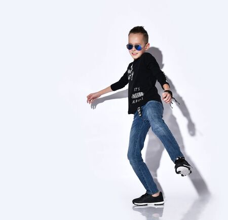 Teenage boy in sunglasses, a black jumper with inscriptions and sneakers, blue jeans, a bracelet. He is dancing while posing isolated on a white studio background. Childhood, fashion.