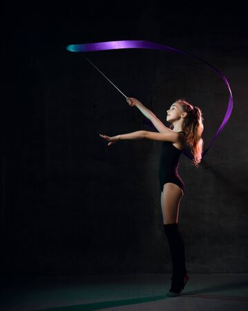 Young girl gymnast in black sport body and uppers standing sideways and making exercise with blue gymnastic tape over dark background. Rhytmhic gimnastics beauty cocnept