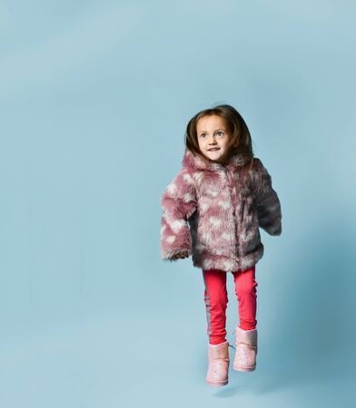 Little girl with bun hairstyle, dressed in pink faux fur coat, pants and boots. She smiling, gesticulating, posing on blue studio background. Childhood, fashion, advertising. Full length, copy space