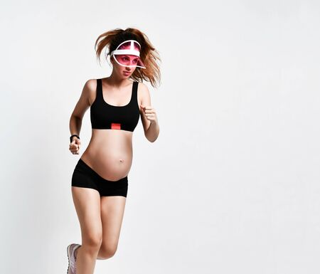 Pregnant lady with belly, in sun visor, black sport shorts and top, pink sneakers. She is smiling while running isolated on white background. Family and maternity concepts. Full-length, copy space Stok Fotoğraf