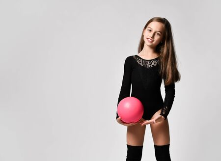 girl gymnast in black body and leggings is training with a pink gymnastic ball. children's professional sport. Rhythmic gymnastics.