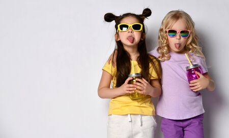 Two little gorgeous girls in sunglasses, colorful casual clothes. They holding cocktail bottles, hugging, showing tongues, posing isolated on white. Childhood, fashion. Full length, copy space