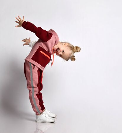 Laughing blonde schoolgirl in pink and red jym suit leaning head forward taking arms back. Sports fashion for children, young athletes, going in for sports. Full length portrait isolated on light grey