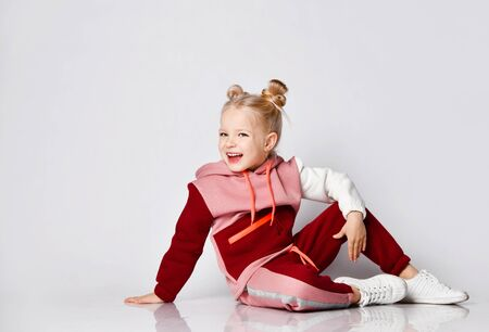 Little blonde girl with buns hairstyle, in colorful tracksuit, sneakers. She laughing, sitting on floor, posing isolated on white. Childhood, fashion, advertising and sport. Close up, copy space