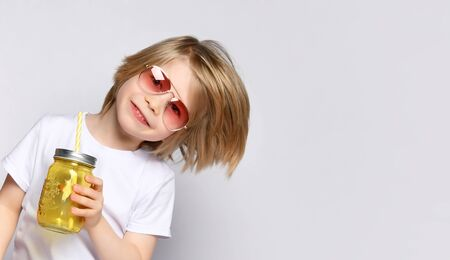Little blond kid in sunglasses and white t-shirt. He is smiling and holding yellow cocktail bottle, posing isolated on white studio background. Childhood, healthy nutrition. Close up, copy space